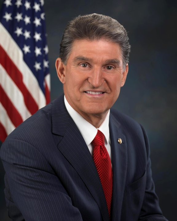 Headshot photo of Joe Manchin sitting in front of American flag.