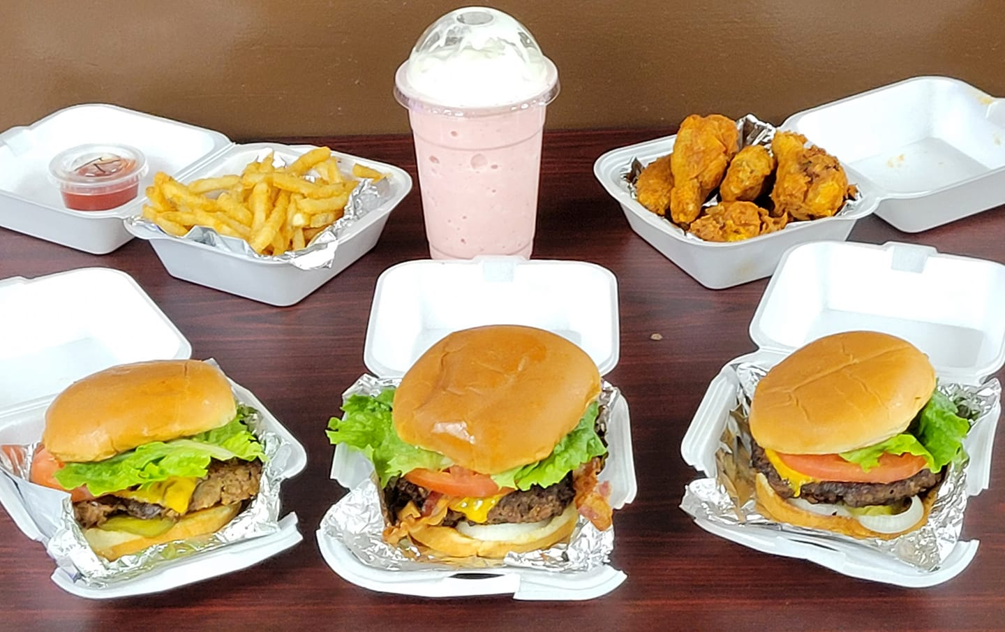 Three burgers, fries, chicken tenders, and a strawberry milkshake sit on a table at Burgers & Bites