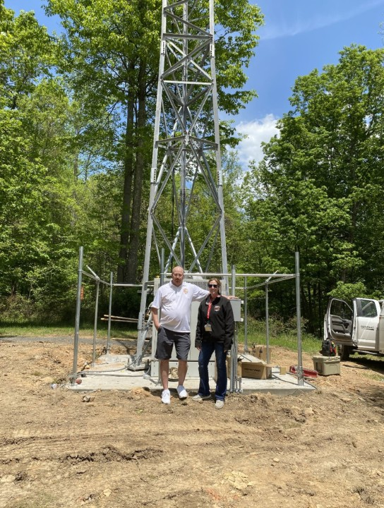 Beverly Cantrell, Tucker County 911 Center Director, is pictured here with Deputy Director Mike Simmons standing at the base of the new Micrologic tower.